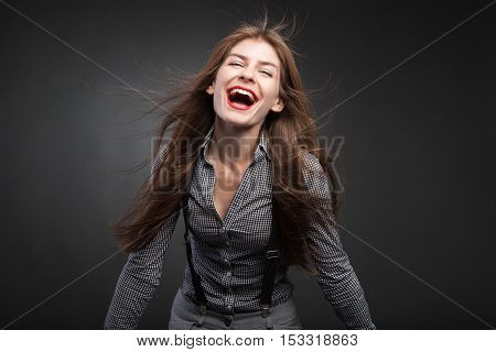 Beautiful women smiling with flying hair and palms outward. Studio portrait on black vignette background.