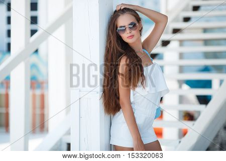 Young beautiful brunette woman with brown long hair,sun glasses,pink lipstick,attractive mole near lower lip,dressed in a short Romper, white,posing outdoors in the summer on the white platform near the white wooden steps