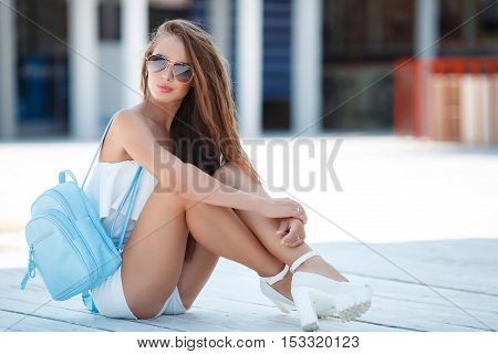 Young beautiful brunette woman with brown long hair, sun glasses, pink lipstick, attractive birthmark near his lower lip, a blue backpack, dressed in a short white suit, posing outdoors in the summer on a white wooden platform