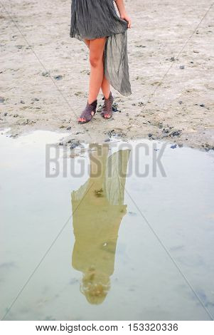 Young woman walking barefoot through puddle outdoors
