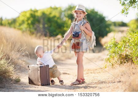 The kid in the white t-shirt and beige shorts with a big old brown suitcase, traveling in the summer on a country road with her older sister, a girl with long braids, wearing a hat, old camera around his neck and a beige backpack