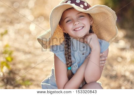 Cute little girl 6 years old,hair braided in two braids,on his head a large straw hat,wearing overalls in the summer gray,in the ears of small earrings,grey eyes and a cute smile posing outdoors in the summer