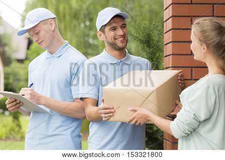 Courier Delivering A Parcel To A Young Woman