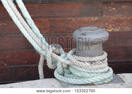 foreground of ropes of a boat tied on a bollard