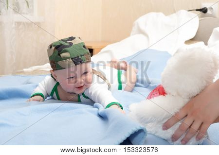 Kid in the bandana plays lying on his stomach