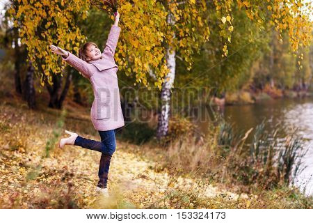 Happy young woman in forest rejoices in autumn