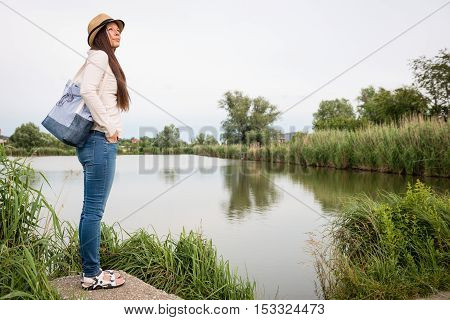 Portrait of young lady with handbag standing by the lake