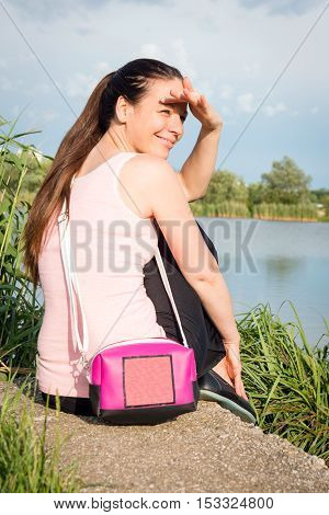 Portrait of young lady in pink shirt with handbag siting by the lake