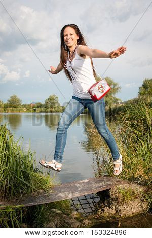 Portrait of young lady in a jeans with handbag jumping by the lake