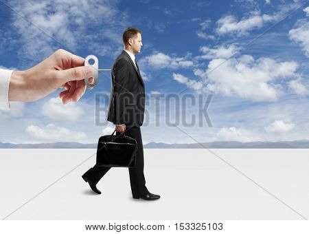 Hand turning winder on business person's back. Sky background. Control concept