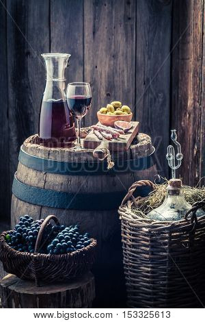 Homemade Red Wine With Olives, Cold Meats, Grapes And Demijohn