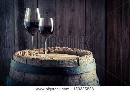 Wine In Glass With Grapes On Old Wooden Barrel