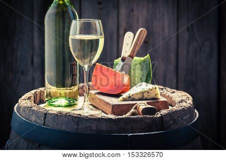 White wine with mix of cheese on wooden barrel