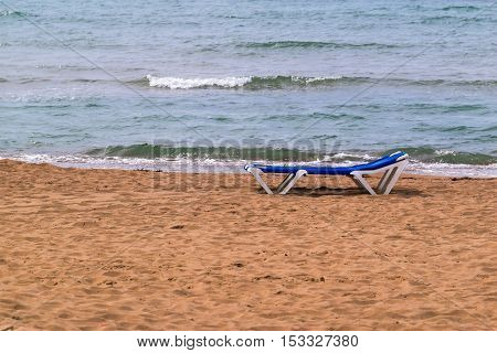 one isolated sunbed on the sandy coast and against the background of a sea surf