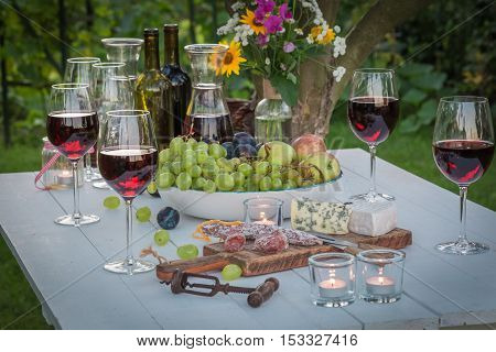 Beautiful Table With Wine And Candles In Garden At Dusk