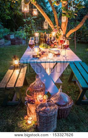 Gorgeous table with wine and candles in garden at dusk