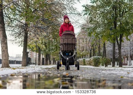 Girl walking with a stroller on alley in autumn park fallen leaves underfoot mud and puddles the first snow.