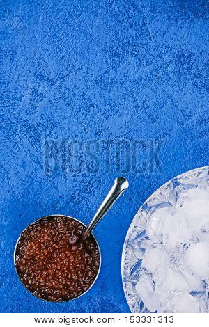 Salted salmon roe in the little steel bowl and ice over spotty blue background. Closeup. Flat lay