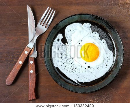 Fork knife and a fried egg in a frying pan