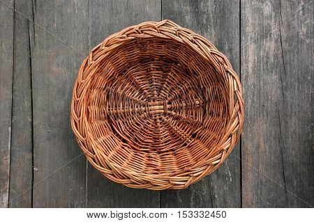 wood weave hand made fruit basket on wood texture table outdoor, in a garden, top view