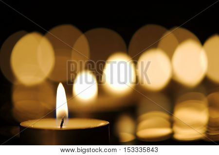 Burning candle against defocused candlelight background. Lights form a diagonal line
