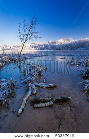Cold Sunrise On Winter Lake Covered With Snow