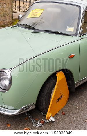 NOTTINGHAM ENGLAND - OCTOBER 22: Nissan Figaro classic car with yellow triangle wheel parking clamp attached. In Nottingham England. On 22nd October 2016.