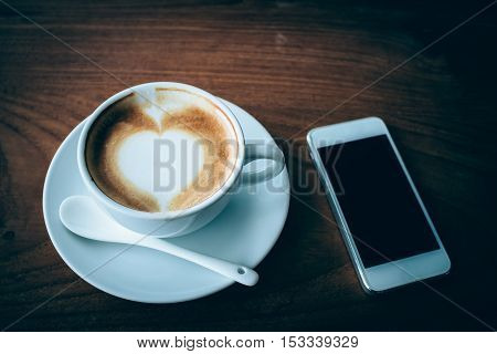 mobile phone and coffee cup on wood table dark tone.