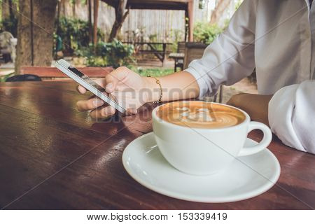 Women use mobile phone with coffee cup vintage tone.