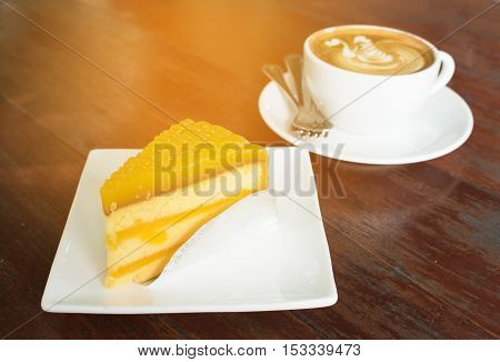 Cake orange and coffee on wood table in coffee shop.