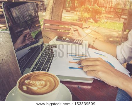 Business women analyzing graph document financial with laptop and coffee vintage tone.