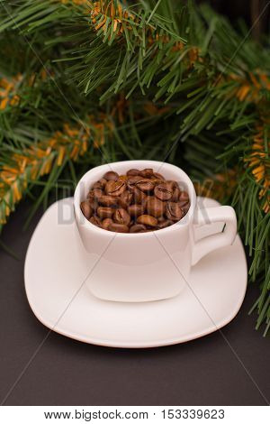 Coffee beans in a white cup and fir branch