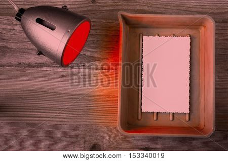 Photographic paper shows up in a cuvette and red laboratory lantern