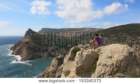 Two people sitting on the edge of a cliff and look down on the sea