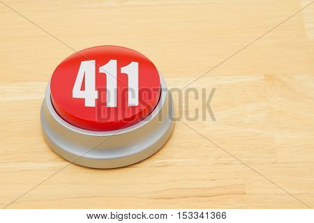 A 411 red push button A red and silver push button on a wooden desk with text 411