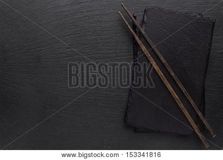 Black slate board and chopsticks on a textured background