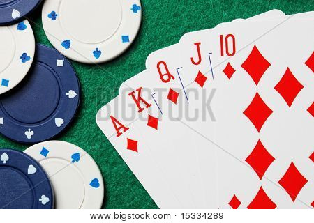 Royal straight flush poker cards with gambling chips on a green felt table background