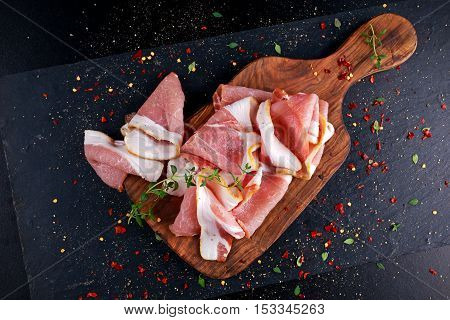 Raw smoked bacon slices on wooden board which herbs.