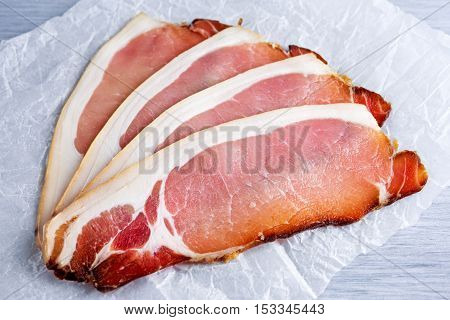 Raw beer bacon slices on crumpled paper which herbs.