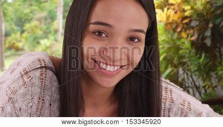 Cute Mexican girl smiling at camera. Sitting outdoors