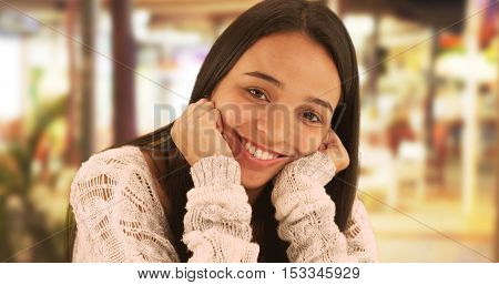 Cute Hispanic woman smiling at camera sitting outdoors