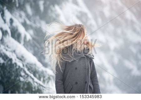 Beautiful young blonde woman in gray coat with fluttering hair covering her face on a walk in winter nature. Snowy day.