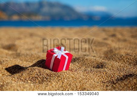 One red gift box on a beach
