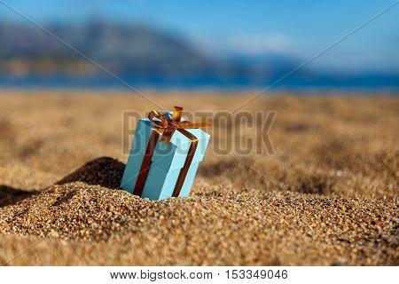 One blue gift box on a beach