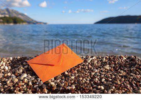 One orange envelope on a gravel beach