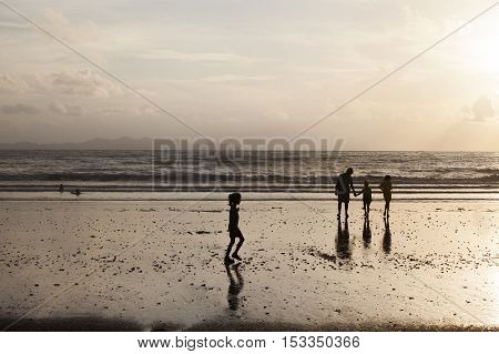 People and sunset at Pak Meng Beach in Trang Thailand.
