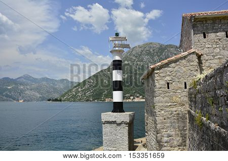 The historic Gospa od Andela Church - Our Lady of the Angels - in Kotor Bay Montenegro. The church is believed to date fom 1584 and has recently been restored. Two islands - Our Lady of the Rock and St George's Abbey - can be seen in the distance alo poster