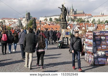 PRAGUE, CZECH REPUBLIK - OCTOBER 21, 2016: Tourists on the Charles Bridge in Prague. The Charles Bridge crosses the river Vltava and connects both parts of the city.