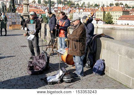 PRAGUE, CZECH REPUBLIK - OCTOBER 21, 2016: Street musicians on the Karlsbrücke in Prague entertain the passing tourists with a concert