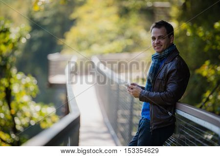 Handsome happy hipster young man using smart phone.